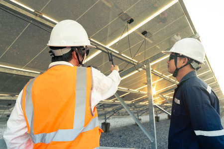 Technician with engineer checks the connection of the solar panels in the solar plant, Alternative energy to conserve the world's energy, Photovoltaic module idea for clean energy production. 免版税图像