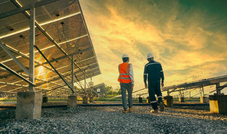 Low angle view of technician walks with investor through field of solar panels, Alternative energy to conserve the world's energy, Photovoltaic module idea for clean energy production. Imagens