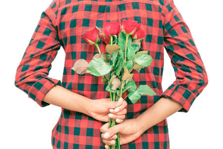 A woman wearing a red and black plaid shirt in her hand holds a red rose hidden behind her to surprise her lover, with white background, Isolated. Banque d'images