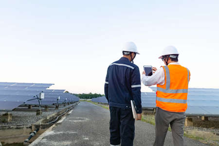 Engineers with investor walk to check the operation of the solar farm(solar panel) systems, Alternative energy to conserve the world is energy, Photovoltaic module idea for clean energy production. 免版税图像
