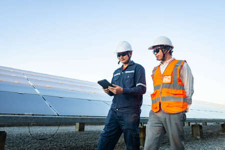 Engineers with investor walk to check the operation of the solar farm(solar panel) systems, Alternative energy to conserve the world is energy, Photovoltaic module idea for clean energy production. Imagens