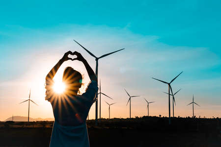 Wind turbines farm is an alternative electricity source, Concept of sustainable resources, Renewable energy concept, Girl standing and watching the sunset with wind generators turbines to backgrounds.
