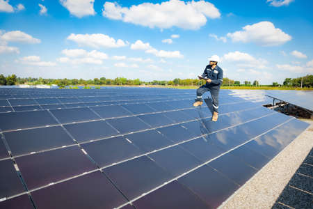 Technician stand on solar panel to check the operation of the solar farm systems, Alternative energy to conserve the world is energy, Photovoltaic module idea for clean energy production.