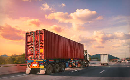 Truck with red container on the highway with sunset time, logistic import export and transport industry concept. Banque d'images