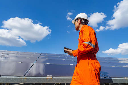 The solar farm(solar panel) with engineers walk to check the operation of the system, Alternative energy to conserve the world's energy, Photovoltaic module idea for clean energy production. Imagens