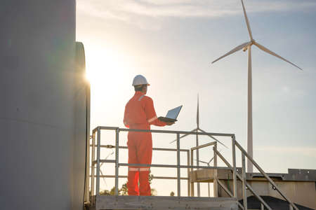 Man engineer working and holding the laptop for check performance of wind turbine farm Power Generator Station, Concept of sustainable resources, Concept of professional for the energy industry.