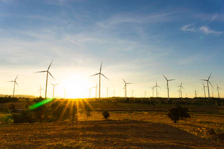 Wind turbines farm is an alternative electricity source, Concept of sustainable resources, Beautiful orange sunlight in summer with wind generators turbines to background, Renewable energy concept.