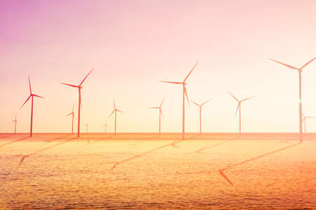 Wind turbines farm on the sea is an alternative electricity source, Concept of sustainable resources, Sunlight in summer with wind generators turbines, Renewable energy concept. Imagens