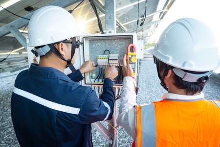 Workers use clamp meter to measure the current of electrical wires produced from solar energy for confirm to normal current. Imagens