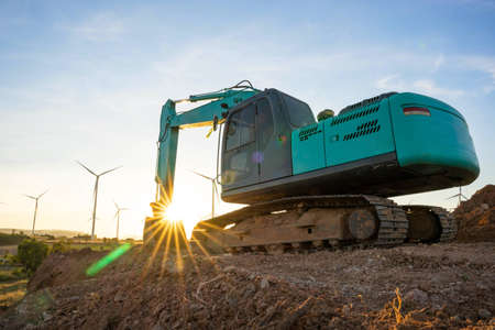 Backhoe and wind turbines that are generating electricity in the background, the concept of sustainable resources, Beautiful sky with wind generators turbines, Renewable energy.