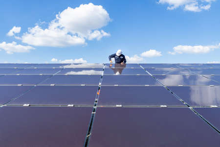 The solar farm with the technician is removing the nut to replace the damaged solar panel, Alternative energy to conserve the world's energy, Photovoltaic module idea for clean energy production. Imagens