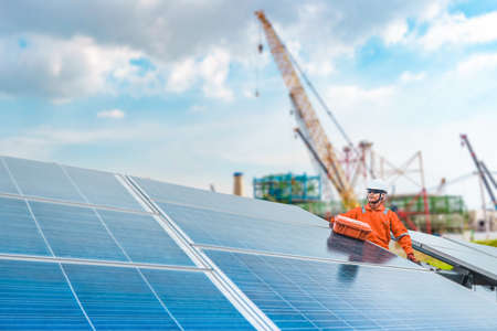 Engineers hold a tool for checking the performance of the solar panel to confirming systems working normally. Photovoltaic module idea for clean energy production, construction is the background.