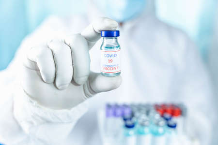 close up a vaccine bottle in the hand of a doctor from the scientific laboratory, a concept of drug use to treat and protect the global COVID-19 pandemic. Banque d'images