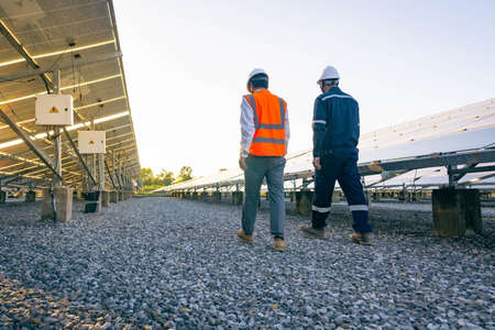 Engineers with investor walk to check the operation of the solar farm(solar panel) systems, Alternative energy to conserve the world is energy, Photovoltaic module idea for clean energy production. Banque d'images