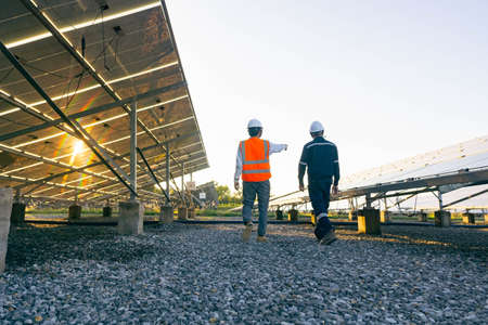 Low angle view of technician walks with investor through field of solar panels, Alternative energy to conserve the world's energy, Photovoltaic module idea for clean energy production. Banque d'images