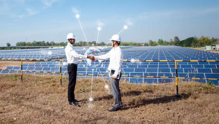 Asian businessmen standing check hand with the solar panel in the background. the idea of investors is cooperating in business on renewable energy to expand their investments around the world.