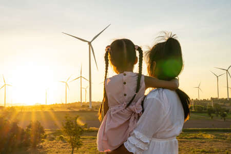 Wind turbines are alternative electricity sources, the concept of sustainable resources, People in the community with wind generators turbines, Renewable energy. Banque d'images