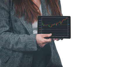 A young businesswoman holds a tablet with a graph showing the ups and downs of her stock. Concept of doing an online business called stock trading that anyone can do if it is learned.