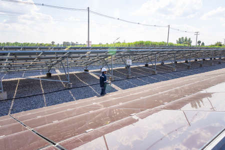 The solar farm(solar panel) with engineers walk to check the operation of the system, Alternative energy to conserve the world's energy, Photovoltaic module idea for clean energy production. Banque d'images
