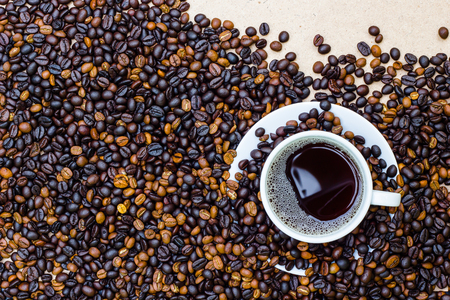 golden bean: Coffee cup and coffee beans on wooden background.