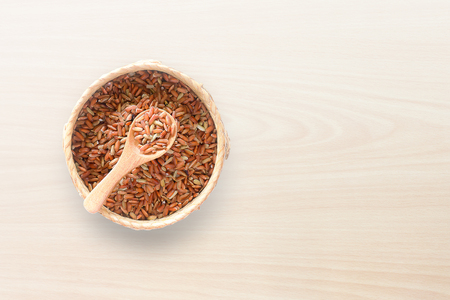 Raw red rice in basket on white wooden background