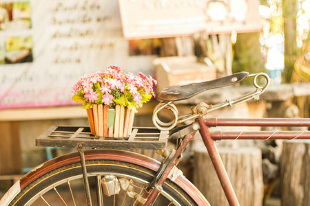 sidewall: Bicycles old vintage flowers in a basket. Parked on the sidewall of the wooden house ideal for design work Classic hoodie style Stock Photo