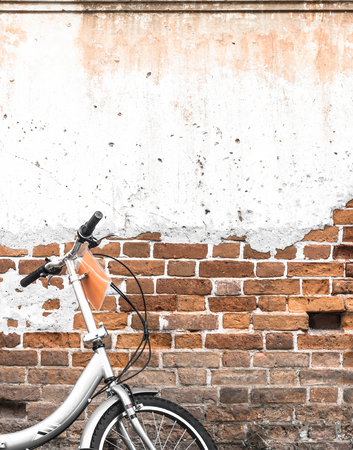 antique furniture: Bicycles old vintage Parked on the red brick wall of the concrete wall ideal for design work Classic hoodie style Stock Photo