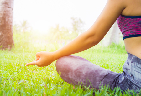 Close-up shots of a young woman practicing yoga in nature. Sit on green grass.Golden light at sunset.Communicate to exercise and maintain good health
