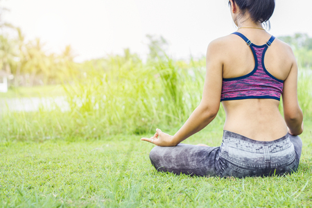 shots of a young woman practicing yoga in nature. Sit on green grass.Golden light at sunset.Communicate to exercise and maintain good health