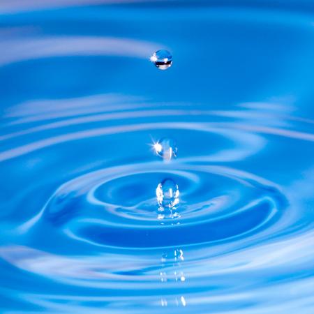 gotas de agua en el agua azul. A continuación, se extendió en pequeños chorros de agua con la luz brillante de las gotas de agua.