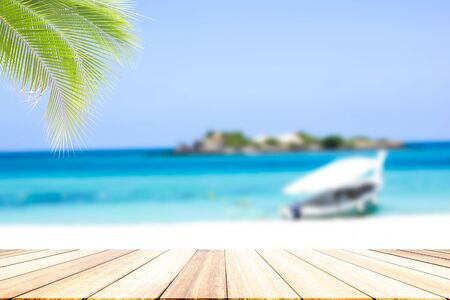 coconut tree In the  perspective wood deck overlook the on blur, white sandy beaches and boats parked on the beach. There is a small island in the middle of the sea in the midday sun. Reklamní fotografie