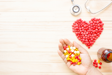 shaped: top view hold antibiotics in hand and stethoscopes placed beside red antibiotics tablets heart shaped on a wooden background, Concept of heart health.