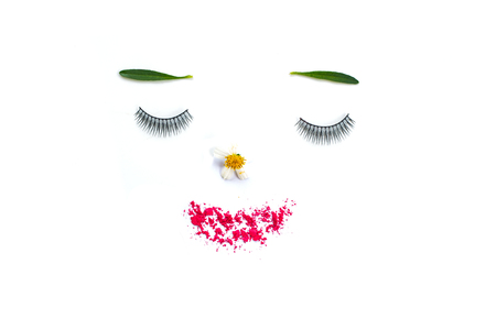 Face of the girl With false eyelashes, leaves, flowers and powder . isolate on white background. Conveys the idea of makeup that emphasizes natural. Or use cosmetics containing natural extracts.