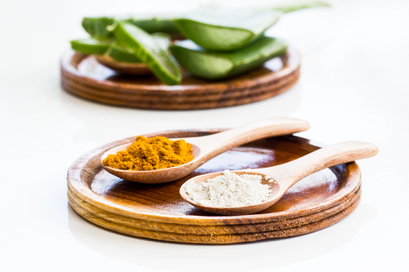 Yellow turmeric powder And the clay powder is placed on a wooden spoon with lemon slices in the back. Put on a white background Turmeric powder mixed with lemon juice, used to nourish the skin, beautiful skin .Used in massage and spa. Stock Photo