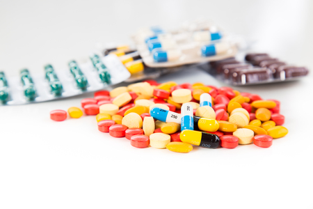 Antibiotics contain blue pills, yellow-red or capsules on a white background with copied clearance. Medication in healthy containers, antibiotics and dangerous drugs.