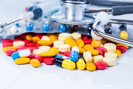 top view color drug , yellow-red or capsules on a white background with copied clearance. Medication in healthy containers, antibiotics and dangerous drugs.Stethoscopes placed beside and placed in a syringe.