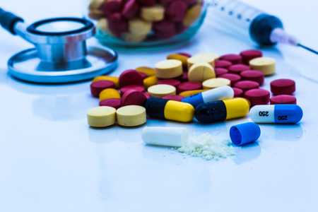 top view color drug contain blue pills, yellow-red or capsules on a white background with copied clearance. Medication in healthy containers, antibiotics and dangerous drugs.