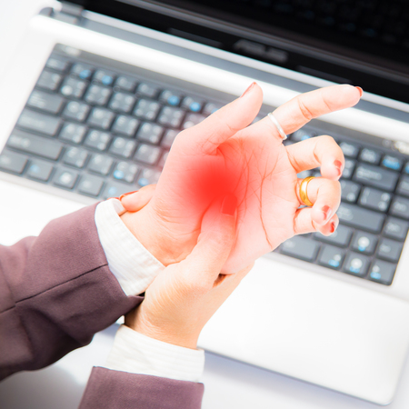 The lock finger of a young businessman sitting with a computer all day. Palm pain from working with a young businessmans computer.