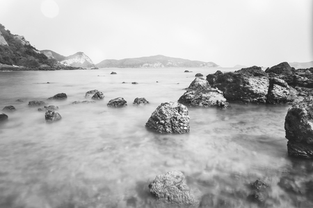 Black and white sea in summer with stones placed on the beach.Summer sea water hits the rocks at sunset and splashes on the island's backdrop.