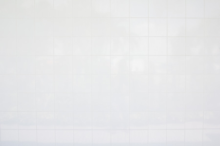 White tile walls inside the office building. There is a small amount of dust sticking to the tile according to the service life. Фото со стока