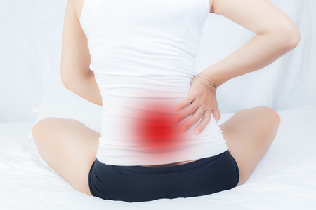 Back pain of women working long hours . Taken from the front view on a white background.