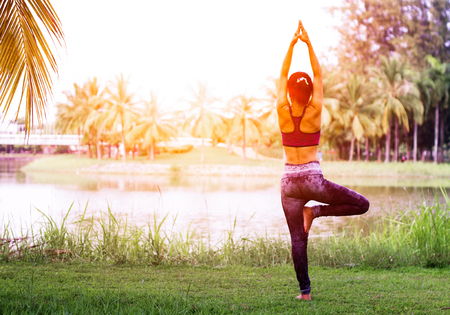 woman practicing yoga in nature. Standing on the green grass .Golden light at sunset.Communicate to exercise and maintain good health