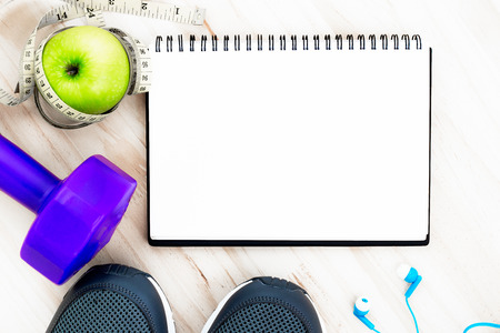 Fitness equipment with weight lifting, waist measurement, shoes and the green apples eat during exercise, put on the wood floor background .Note pad space for text input on health care and fitness.