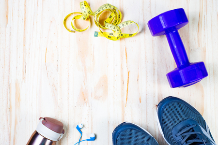 Exercise equipment use to wear workout have Drink water,measuring tape Waistline,running shoes and Sports bra on wood floor background.Copy space for text input on health care and fitness.