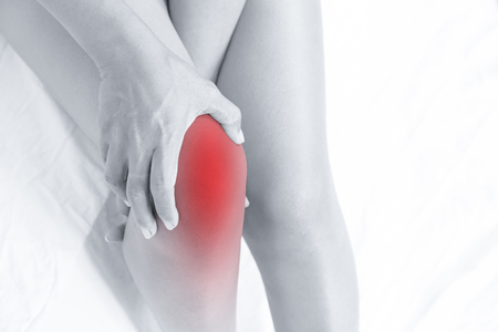close up young woman massaging her painful knee . Pain relief concept