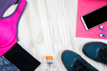 Womens Exercise Dress Red shirt and black pants Use to wear a workout. Drinking water, headphones and Clock uses timer Placed on a white background.