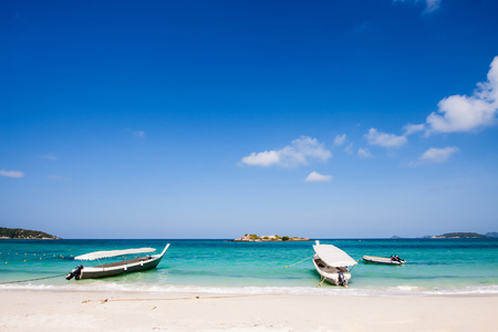 Beautiful white clouds on blue sky over calm sea with sunlight reflection sea beach.Surrounded by clear turquoise sea.White sand under the sea Tourist boat Parked on the beach.