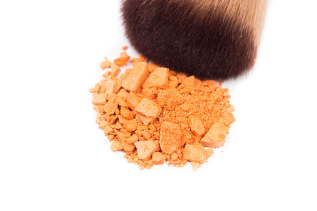Close-up Cheek brushes and orange colour cosmetic powder isolated on white background.Use the makeup concept.