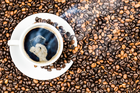 coffee cup and coffee beans on wood texture background. View from top and free space for text.