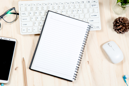 Wooden desk with computer white keyboard . Notebook  are placed on the white background. Note pad space for text input.